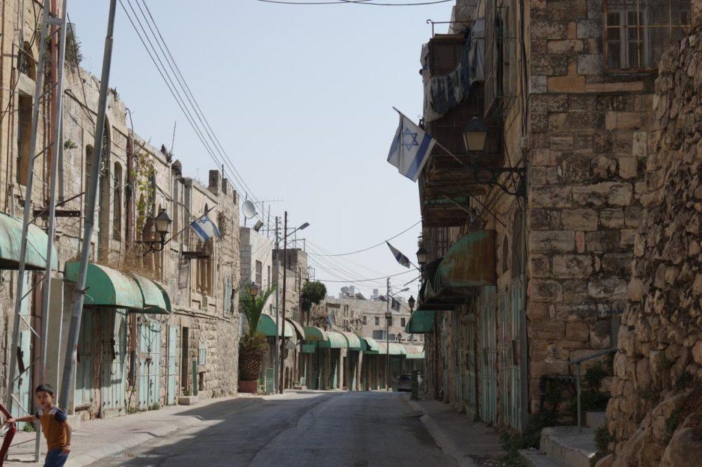 L'accès à cette rue d'Hebron a été interdit aux Palestiniens. Les colons achètent petit à petit les maisons, ou les occupent sans permission pour agrandir la colonie située au coeur de la ville. Les drapeaux israéliens flottent en fait illégalement sur des maisons palestiniennes.